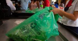 Pessoa embala compras em um saco verde que remete à nova lei de sacolas plásticas