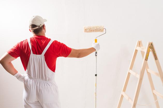 pintor com rolo e escada, se preparando para pintar parede