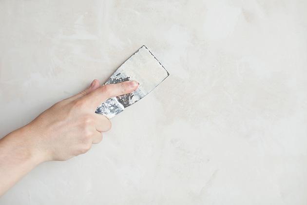 pessoa lixando a parede da empresa e realizando limpeza e proteção