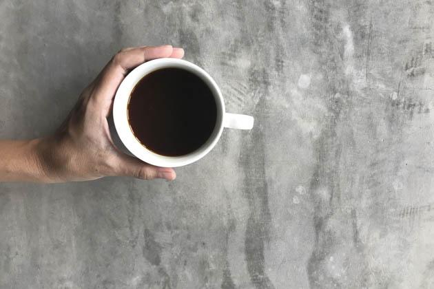 Xícara de café sobre o chão de cimento queimado
