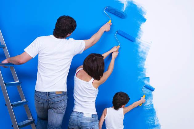 Pai, mão e filha fazem uma pintura de parede em casa